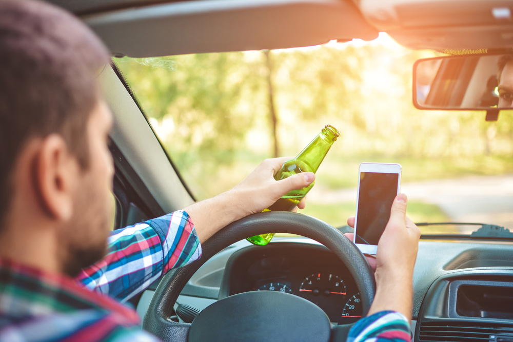 Man texting and drinking while driving. DWI Defense